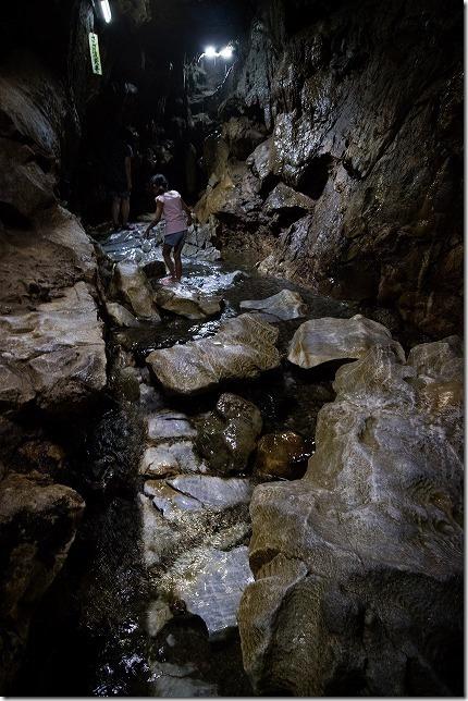 平尾台の水の中を進む千仏鍾乳洞と子供